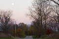 Moonrise over a rural back road the near full moon rising country lines with autumn colored trees and the bright green grass with Royalty Free Stock Image