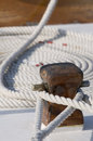 Moored boat detail of a sailboat deck with two ropes tied up on a bitt and one rolled rope in background Stock Image