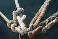 Mooring knots rusted ring with naval ropes on the pier Royalty Free Stock Photos