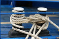 Mooring rope with a knotted close up of end tied around cleat on wooden pier nautical Royalty Free Stock Images