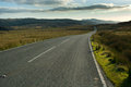 Moorland road passing across remote photographed in the late evening sun Royalty Free Stock Photography