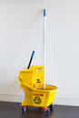 Mop bucket and wringer with caution sign on black floor in office building Royalty Free Stock Photography