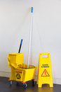 Mop bucket and wringer with caution sign on black floor in office building Stock Photos