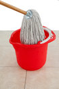 Mop in red bucket on tile floor Royalty Free Stock Photo