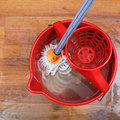 Mop and red bucket top view of cleaning of wood floors by Stock Photo