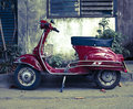 Moped parked old red toned image Royalty Free Stock Photos
