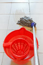 Mopping the tile floor by swab and red bucket Royalty Free Stock Photo