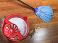 Mopping of wooden floors and red bucket with washing water Stock Photo
