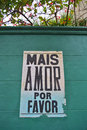 More love please banner sign mais amor por favor poster in a green wall Stock Photography