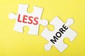 Less and more words printed on two pieces of puzzle Royalty Free Stock Photos