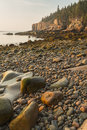 Morning on acadia boulder beach rounded stones looking toward the otter cliffs at sunrise in national park maine Stock Photos
