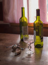 Morning after booze-up two empty bottles of red wine and glass t Royalty Free Stock Photo