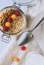 Morning breakfast, oatmeal with red and yellow raspberries and walnuts in a glass ja Royalty Free Stock Photo