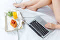The morning and breakfast of young beautiful girl in bed at home with laptop s legs closeup Royalty Free Stock Photo