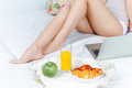 The morning and breakfast of young beautiful girl in bed at home with laptop s legs closeup Stock Photos