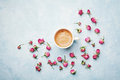 Morning coffee cup and dry rose flowers on blue vintage table top view in flat lay style. Cozy breakfast on Mother or Woman day. Royalty Free Stock Photo