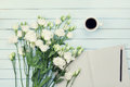 Morning coffee cup, empty paper list, pencil, and bouquet of white flowers eustoma on blue rustic table overhead view. Flat lay. Royalty Free Stock Photo