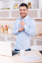 Morning dress up happy young man adjusting sleeves on his shirt and looking at camera while standing in the kitchen Royalty Free Stock Photography