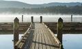 Morning fog on dock hanging over calm lake Stock Photos