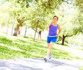 Morning jog full length of young woman in sportswear jogging at park horizontal shot Royalty Free Stock Images