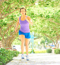 On a morning jog full length of young woman in sportswear jogging at park vertical shot Royalty Free Stock Photography