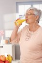 Morning juice old lady drinking orange in the Royalty Free Stock Images