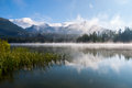 Morning mist above Strbske pleso mountain lake