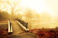 Morning pond fog and golden light with footbridge of Royalty Free Stock Photos
