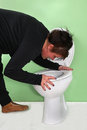 Morning sickness pregnant woman throwing up over toilet in bathroom Royalty Free Stock Images
