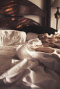 Morning sunlight on an unmade luxury bed of white sheets and bla Royalty Free Stock Photo