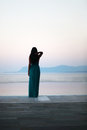 Morning view at the infinity pool classy lady gazing horizon on edge of an woman is wearing a beautiful long turquoise dress Stock Image