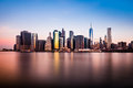 Morning view of lower Manhattan silhouette reflexing in the clear waters of East River Royalty Free Stock Photo