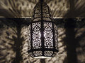 Moroccan ornate pierced metal filigree lamp casting intricate shadows wall Stock Photo