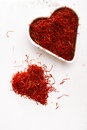 Moroccan saffron treads in pile on white wood heart shallow dof Stock Photography