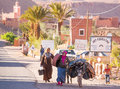 Moroccan womans with a donkey carrying heavy loads in ait ben haddou morocco Royalty Free Stock Photos