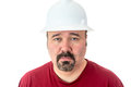 Morose glum looking man in a hardhat with goatee beard wearing at the camera with lacklustre eyes and depressed Royalty Free Stock Photos