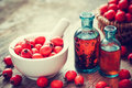 Mortar of hawthorn berries two tincture bottles and thorn apple apples in basket on old wooden table herbal medicine selective Stock Image
