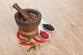 Mortar and pestle with red hot chili pepper and peppercorn on wooden table Royalty Free Stock Image