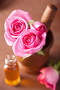 Mortar with rose flowers essential oil for aromatherapy and and spa Royalty Free Stock Images