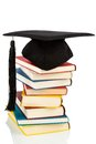 Mortarboard on books stack a a book symbol photo for education and skills Stock Photos