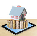 Mortgage concept by money house from coins and tablet Stock Image