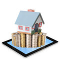 Mortgage concept by money house from coins and tablet Royalty Free Stock Photos