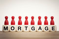 Mortgage concept red pawns on the word spelled by toy dice Royalty Free Stock Photos