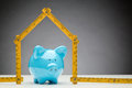 Mortgage savings and new home a blue ceramic piggy bank under a measurement tape in the shape of a house concept about Royalty Free Stock Images
