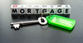 Mortgage text on small white cubes in black uppercase letters with key and green tag Stock Photos