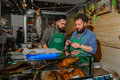 Moscow, Russia - February 25, 2017: Two bearded seller of dried and smoked fish at the time of the break at work on fair