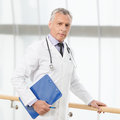 The most talented and professional doctor confident mature doct standing with a clipboard looking at camera Royalty Free Stock Image