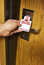 Motel insert into lock sign most motels have do not disturb signs to put on the room doors a man's hand is removing or putting Stock Image
