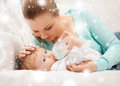 Mother and adorable baby with feeding-bottle Stock Image