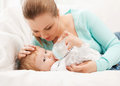 Mother and adorable baby with feeding-bottle Stock Photos